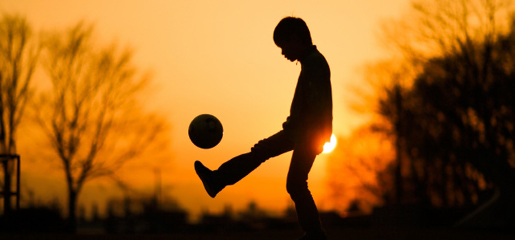 夕暮れにサッカーをする少年